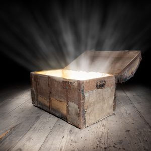 Ancient wooden treasure chest with the strong glow from inside.
